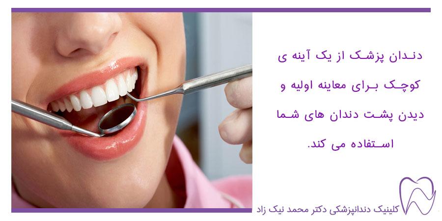 دندانپزشک با یک آینه کوچک پشت دندان ها را معاینه میکند